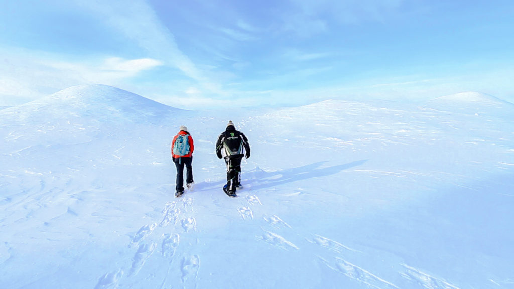 Sean and Q walk in snowshoes up ice dune.