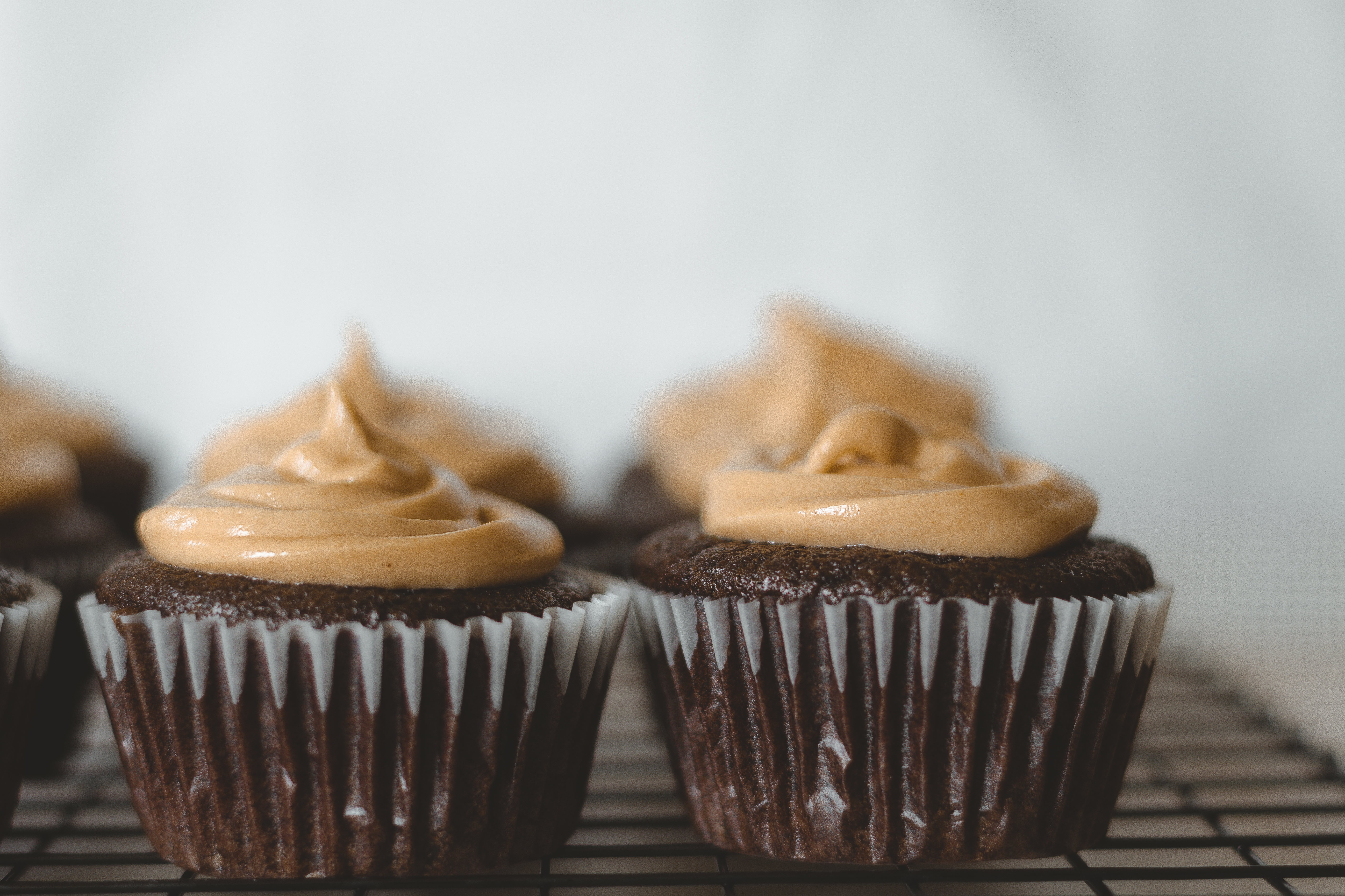 Close up of 2 cupcakes on a cooling rack.