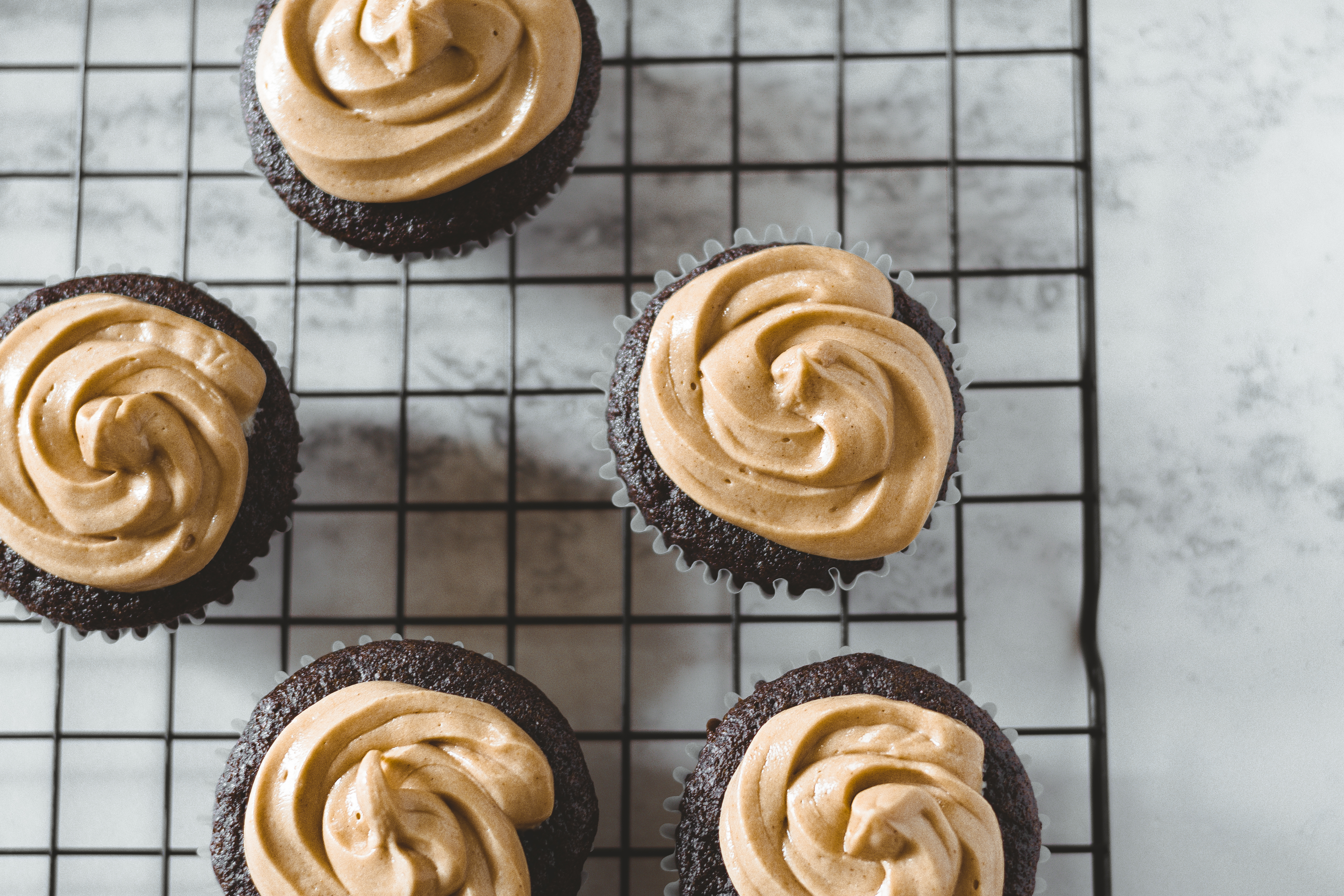 A top view of 5 chocolate cupcakes on cooling rack