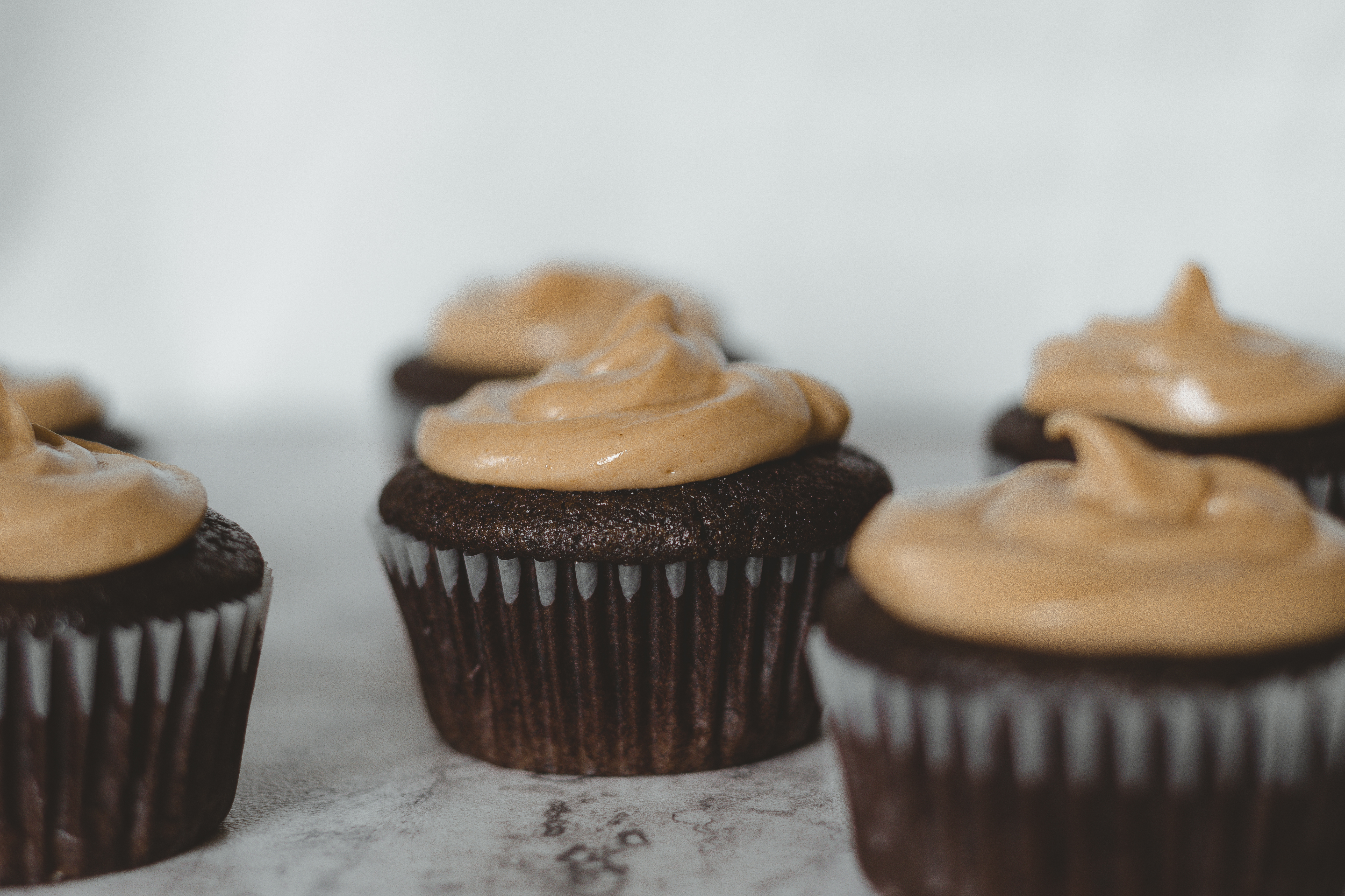 45 degree angled shot of cupcakes on marble countertop.